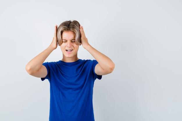 Jonge tienerjongen met handen op oren in blauw t-shirt en geïrriteerd, vooraanzicht.