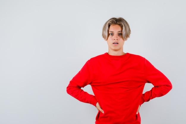 Jonge tienerjongen met handen op taille in rode trui en verbijsterd kijkend, vooraanzicht.