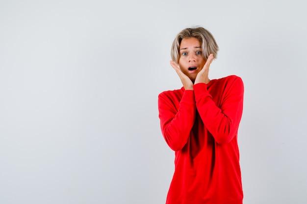 Jonge tienerjongen met handen op wangen in rode trui en bang, vooraanzicht.