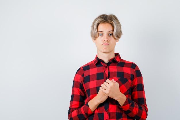 Jonge tienerjongen met handen over borst in geruit overhemd en teleurgesteld, vooraanzicht.