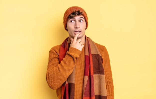 Jonge tienerjongen met verbaasde, nerveuze, bezorgde of bange blik, opzij kijkend naar kopieerruimte