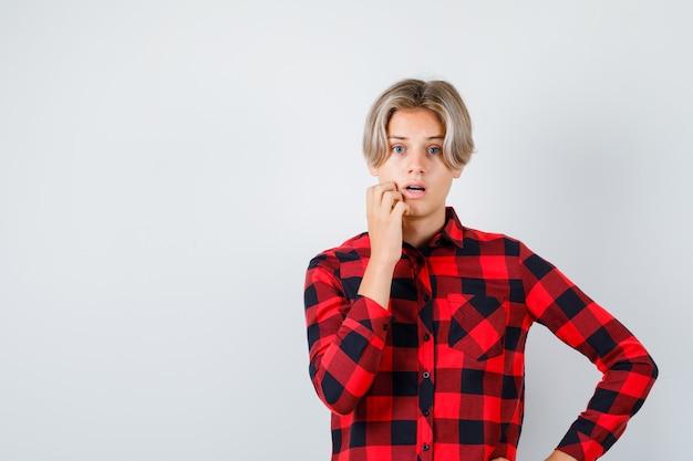 Jonge tienerjongen staat in denkende pose in geruit overhemd en kijkt verbijsterd, vooraanzicht.