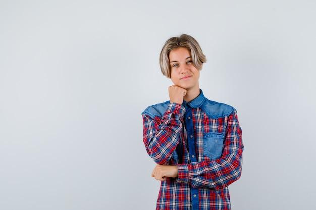 Jonge tienerjongen steekt kin op vuist in geruit overhemd en ziet er vrolijk uit