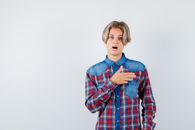 Jonge tienerjongen wijst naar rechts in geruit overhemd en kijkt geschokt