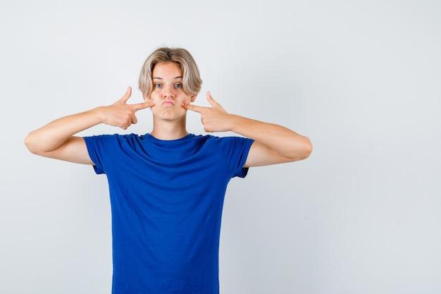 Jonge tienerjongen wijst naar zijn gezwollen wangen in blauw t-shirt en kijkt verbaasd. vooraanzicht.