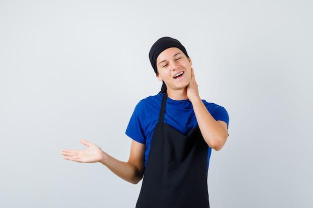 Jonge tienerkok in t-shirt, schort met hand op nek, palm opzij spreidend en peinzend kijkend, vooraanzicht.