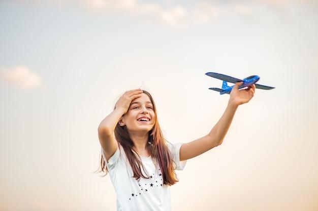 Jonge tienermeisje bedrijf vliegtuig. stuk speelgoed vliegtuig op de achtergrond van de hemel ter beschikking. droom. vrijheid