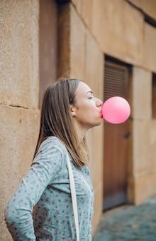 Jonge tienermeisje blaast roze kauwgom