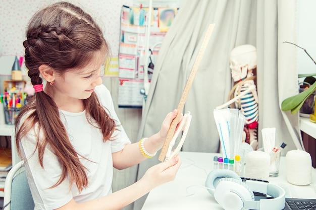 Jonge tienermeisje dat de menselijke anatomie thuis bestudeert. ze meet het bot van de arm. ongewone hobby.