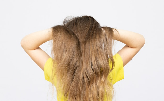 Jonge tienermeisje sluit haar oren achteraanzicht geïsoleerd op wit