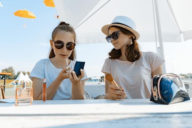 Jonge tienermeisjes die pret in een openluchtkoffie hebben