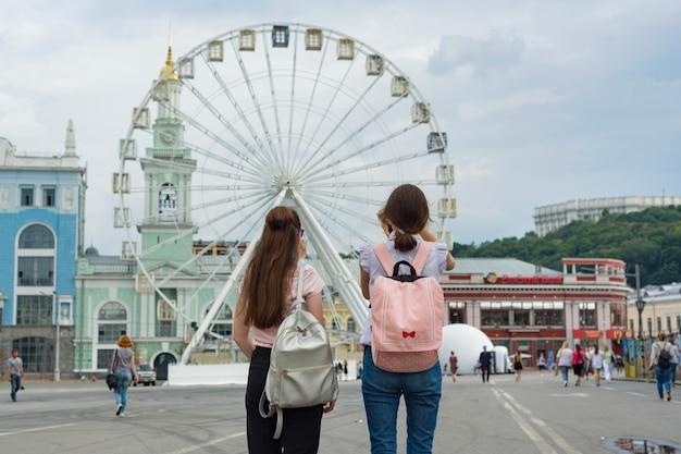 Jonge tienermeisjes lopen in de stad. achtergrond reuzenrad