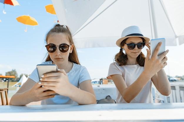 Jonge tienermeisjes met mobiele telefoons