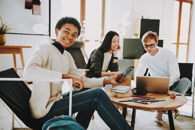 Jonge tieners zitten in fauteuils in coworking place.