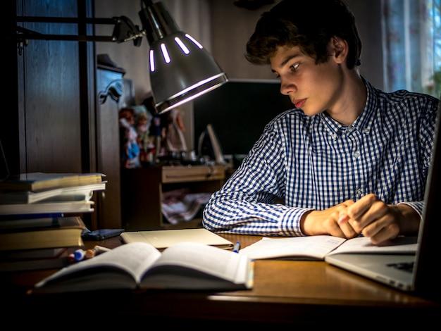 Jonge tienerschooljongen aan de tafel huiswerk in de donkere kamer