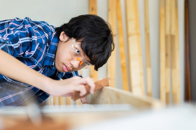 Jonge timmerman bezig met houtbewerking in timmerwerkplaats, timmerman werkt het hout met het schuurpapier