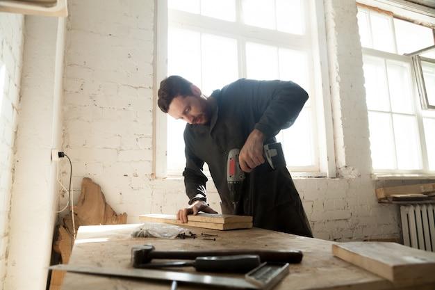 Jonge timmerman doet houtwerk in timmerwerk
