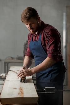 Jonge timmerman met een schort in zijn atelier