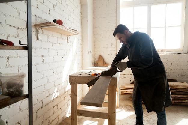 Jonge timmerman snij houten plank met handzaag in de werkplaats