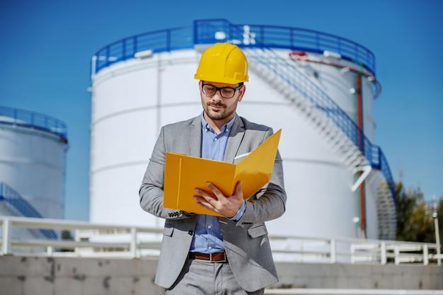 Jonge toegewijde kaukasische zakenman in pak met helm op hoofd houden map met document en het analyseren van de ineenstorting van de olieprijs op de beurs.