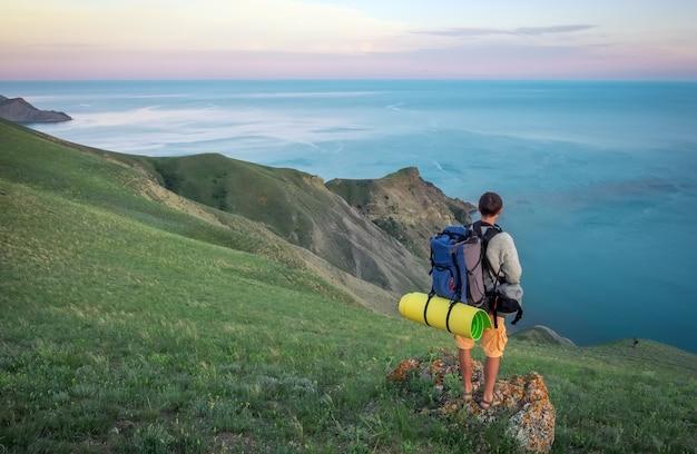 Jonge toerist bovenop een berg die van zeezicht geniet.