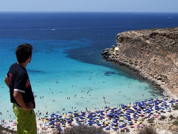 Jonge toerist kijkt naar het prachtige strand van konijnen in lampedusa, sicilië