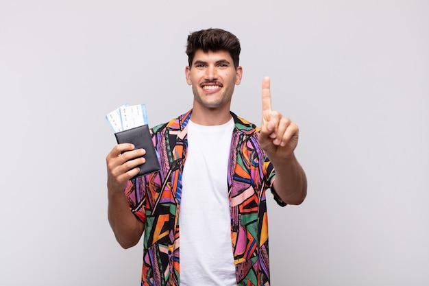 Jonge toerist met een paspoort dat vriendelijk glimlacht en er vriendelijk uitziet, nummer één toont of eerst met de hand naar voren, aftellend