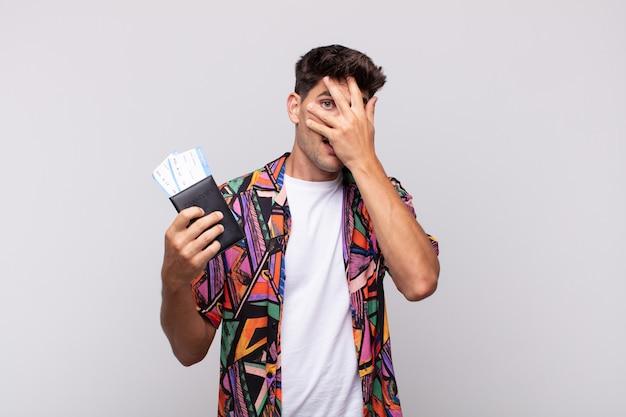 Jonge toerist met een paspoort die er geschokt, bang of doodsbang uitziet, het gezicht bedekt met een hand en tussen de vingers gluurt