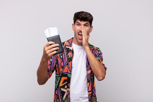 Jonge toerist met een paspoort die zich gelukkig, opgewonden en positief voelt, een grote schreeuw geeft met handen naast de mond, roept