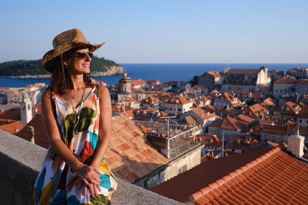 Jonge toerist met hoed en glazen bij zonsondergang in oude stad dubrovnik, kroatië
