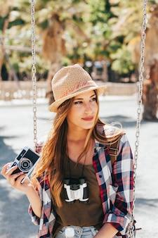 Jonge toerist poseren met camera op de schommel