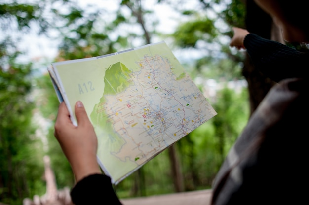 Jonge toeristen en een kaart met een glimlach reizen graag naar verschillende locaties.