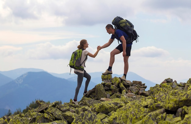 Jonge toeristen met rugzakken, atletische jongen helpt slank meisje om rotsachtige bergtop tegen heldere zomerhemel en bergketen te beklimmen