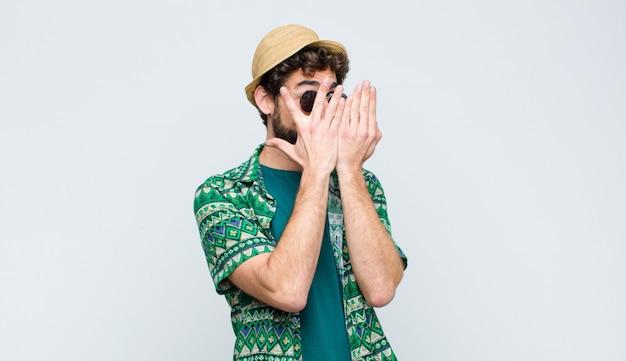 Jonge toeristenmens die gezicht bedekt met handen, tussen vingers gluurt met verbaasde uitdrukking en opzij kijkt tegen een witte muur