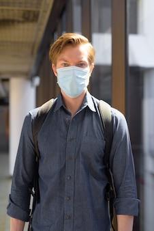 Jonge toeristenmens die met masker reist voor bescherming tegen uitbraak van het coronavirus op de luchthaven