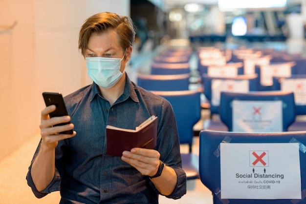 Jonge toeristenmens die met masker telefoon en paspoort controleren zittend met afstand op de luchthaven