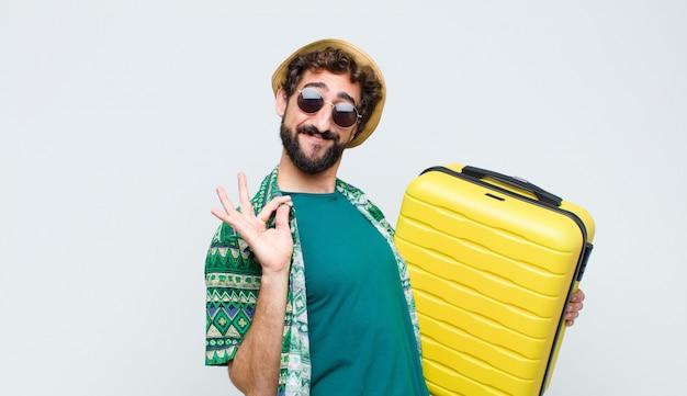Jonge toeristenmens met een koffer op witte muur. reis concept