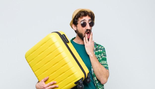 Jonge toeristenmens met een koffer tegen witte muur. reizen concept