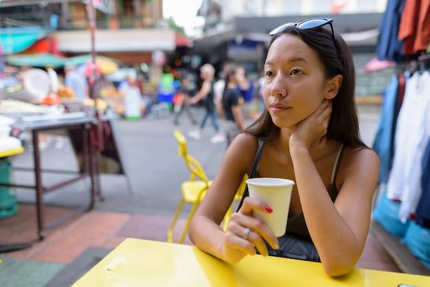 Jonge toeristenvrouw die de stad van bangkok onderzoekt