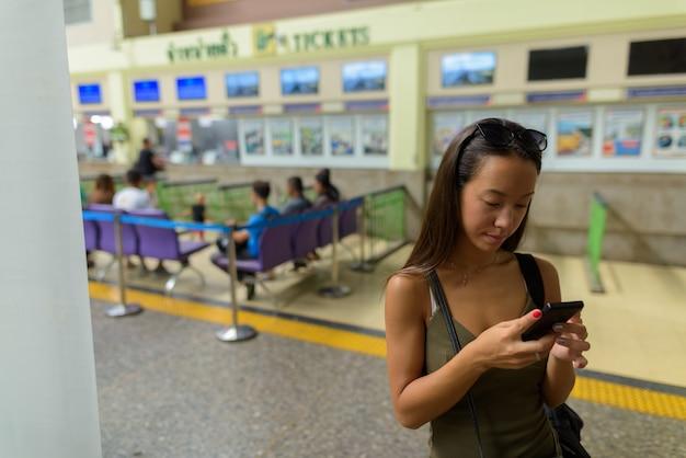 Jonge toeristenvrouw die de stad van bangkok op treinstation onderzoekt