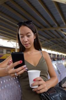 Jonge toeristenvrouw die koffie hebben en mobiele telefoon met behulp van