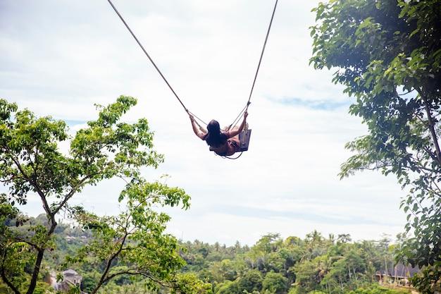 Jonge toeristenvrouw die over het tropische regenwoud bij het eiland van bali slingert