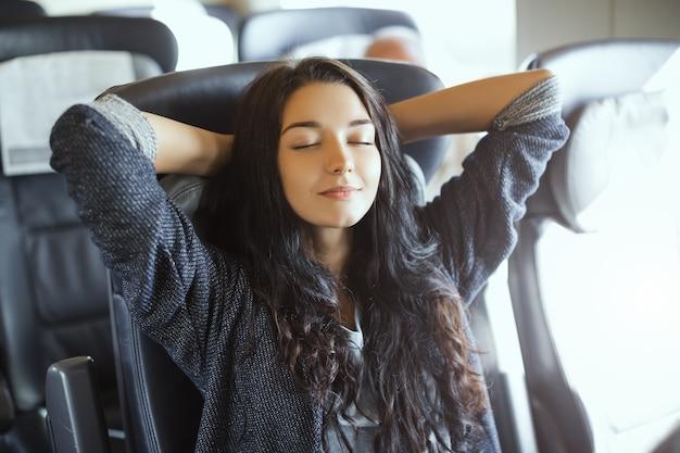 Jonge toeristenvrouw die zittend in de trein reist. schitterend gelukkig gemengd ras aziatisch kaukasisch