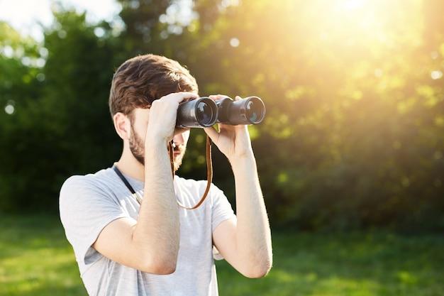 Jonge toeristische ontdekkingsreiziger die door verrekijkers in afstand kijkt die onbekende plaatsen verkent. reiziger die door verrekijkers kijkt