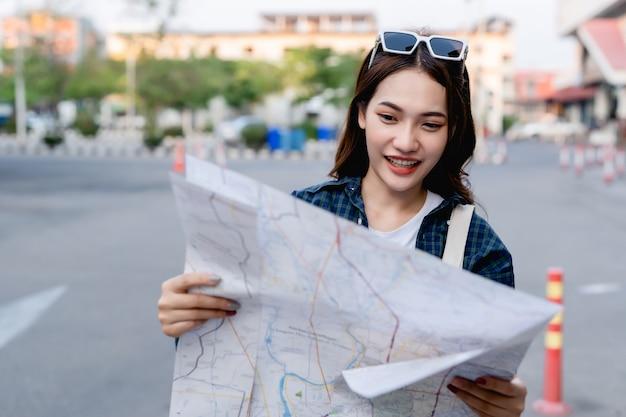 Jonge toeristische vrouw die een papieren kaart vasthoudt en controleert, ze kijkt en glimlacht van geluk