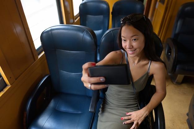 Jonge toeristische vrouw zit op trein tijdens het gebruik van telefoon