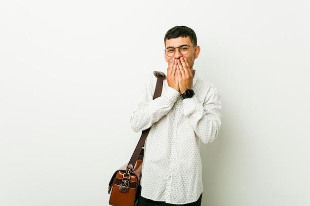 Jonge toevallige bedrijfsmens die om iets lacht, die mond behandelt met handen