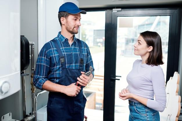 Jonge toevallige huisvrouw die technicus of loodgieter bekijkt alvorens hem probleem met keukenmateriaal uit te leggen