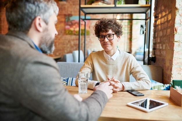 Jonge toevallige onderneemster die in oogglazen collega tijdens bespreking van werkogenblikken bekijken