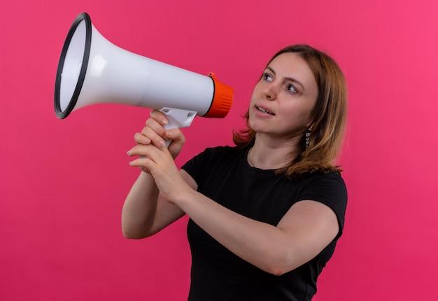 Jonge toevallige vrouw die door spreker spreekt die naar linkerkant op geïsoleerde roze muur kijkt